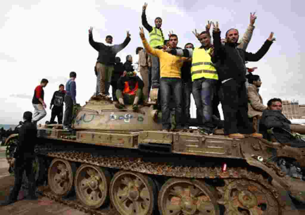 Anti-government protesters make victory signs as they stand on an army tank near a square where people protest in Benghazi city, February 24, 2011