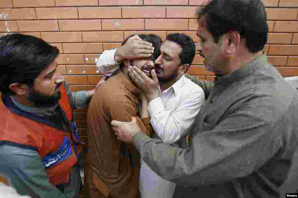 A man is comforted by a relative as he mourns for a family member, killed in a bomb attack in Jalozai camp, outside Lady Reading Hospital in Peshawar, Pakistan, March 21, 2013.