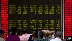 Inversores chinos monitorean la Bolsa de Valores de Beijing ante las profundas caídas el lunes, 24 de agosto de 2015.