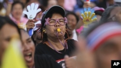 An anti-government protester blows a whistle during a rally at the Democracy Monument in Bangkok, Thailand, Friday, Dec. 6, 2013. The truce between Thailand's political rivals held in Bangkok on Friday amid more ceremonies in honor of the king's birthday,