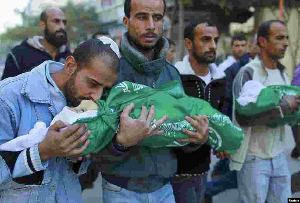 Một người đàn ông Palestine hôn thi hài của con trong tang lễ ở phía Bắc Dải Gaza, ngày 18/11/2012.