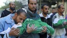 A Palestinian man kisses the body of one of his children during their funeral in the northern Gaza Strip, November 18, 2012. (Reuters)