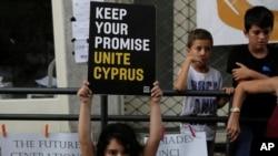 Seorang anak perempuan mengangkat poster dengan pesan perdamaian selama unjuk rasa damai di Ladras atau titik perlintasan Lokmachi yang menghubungkan Siprus Yunani bagian Selatan dan Siprus Turki di Utara, di dalam zona penyangga PBB di ibukota yang terbagi dua, Nikosia, Siprus, Kamis, 6 Juli 2017 (foto: AP Photo/Petros Karadjias)