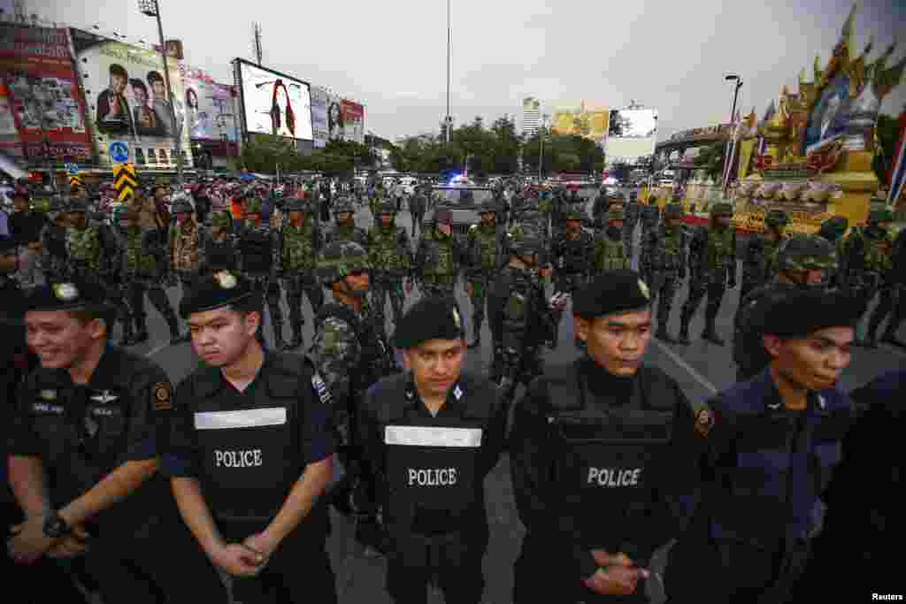 Police officers and soldiers stand guard during a protest against military rule at Victory Monument in central Bangkok, May 26, 2014.