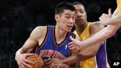 Newly-acquired New York Knicks guard Jeremy Lin (L) is fouled by Los Angeles Lakers' Andrew Goudelock (R) during second half of an NBA basketball game in Los Angeles December 29, 2011.