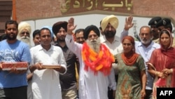 Released Indian prisoner Surjeet Singh (C), accompanied by son Kulwinder Singh (2nd L), waves after returning to his home country from Pakistan at the Wagah border on June 28, 2012.