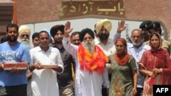 Released Indian prisoner Surjeet Singh (C), accompanied by son Kulwinder Singh (2nd L) and daughter Parwinder Kaur (2nd R), waves after returning to his home country from Pakistan at the Wagah border, June 28, 2012.