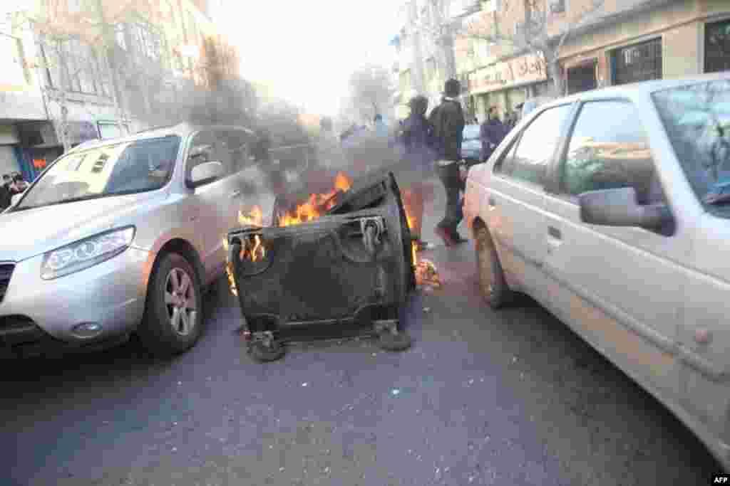 A dumpster burns on a street near Azadi Square in Tehran