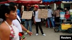 """Para migran Venezuel memegang poster-poster bertuliskan """"Kami warga Venezuela mencari bantuan dan pekerjaan, Tuhan memberkati Anda,"""" di perbatasan Venezuela dengan Ekuador, di Tumbes, Peru, 24 2018."""