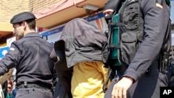 Dalam foto tertanggal 27/3/2012 ini tersangka anggota al-Qaida yang wajahnya ditutup jaket digiring oleh polisi di Valencia, Spanyol. Jumat (30/5/2014) polisi menangkap 6 anggota al-Qaida berkewarganegaraan Spanyol.