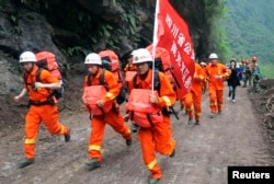 2013年4月21日,在一次地震袭击四川雅安地区的第二天,救援人员快速通过瓦砾抵达被孤立的宝兴县灾区。