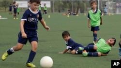 El menor Toby Rafique (izquieda) lleva el balón en la escuela del Barcelona en Florida, Estados Unidos.