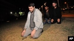 Tres de los cuatro ex prisioneros oran frente a la embajada de EE.UU en Uruguay durante su protesta pacífica.