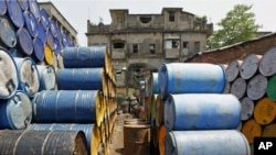A labourer works amid oil containers at a wholesale fuel market in Kolkata, India, April 7, 2011.