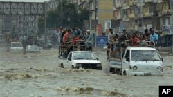 FILE - Pakistani commuters travel on a flooded street following a heavy rainfall in Karachi, Pakistan, Aug. 31, 2017.