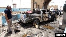 Seorang warga berdiri di TKP bom bunuh diri di pos pemeriksaan polisi di distrik sebelah utara kota Baghdad, Irak.