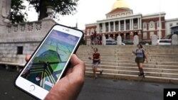 Seorang pemain Pokemon Go melihat ponselnya sambil berjalan melalui di luar gedung pemerintah di Boston, Massachusetts (18/7). (AP/Charles Krupa)