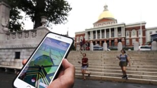 A Pokemon Go player consults his phone while walking through the Boston Common outside the Massachusetts Statehouse. The game has introduced players to some aspects of history they otherwise might have missed.