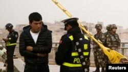 រូបភាពឯកសារ៖ ប៉ូលិសម្នាក់ឆែកអត្តសញ្ញាណបណ្ណបុរសម្នាក់ខណដែលកងកម្លាំងសន្តិសុខត្រួតពិនិត្យផ្លូវនៅតំបន់ Xinjiang កាលពីថ្ងៃទី២៤ ខែ មីនា ឆ្នាំ ២០១៨។