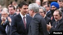 El primer ministro Stephen Harper, derecha, saluda al wider liberal, Justin Trudeau, quien según las encuestas podría sustituirle este lunes.
