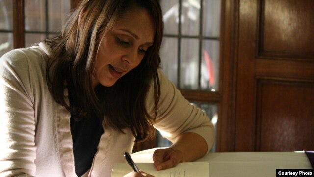 Pulitzer Prize-winning Natasha Trethewey, the new U.S. poet laureate, a  signs a copy of her book Native Guard. (Photo Credit: Jalissa Gray)