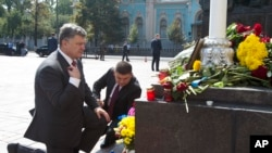 在基辅议会大厦前乌克兰总统波罗申科(左)在周一冲突中死亡的国民卫队军官的照片前献花。 (2015年9月1日)