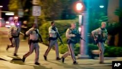 FILE - Police run toward the scene of a shooting near the Mandalay Bay resort and casino on the Las Vegas Strip in Las Vegas, Oct. 1, 2017.