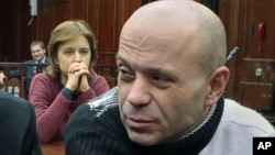 Politkovskaya's daughter Vera, background, looks at former police officer Dmitry Pavlyuchenko, right, prior to the judge's verdict, at the Moscow City Court, Russia, December 14, 2012