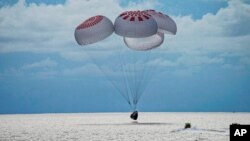 In this image provided by SpaceX, a capsule carrying four people parachutes into the Atlantic Ocean off the Florida coast, Sept. 18, 2021.