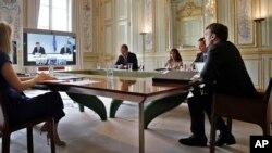 Francuski predsednik Emanuel Makron, desno, prisustvuje onlajn sastanku sa premijerom Kosova Avdulahom Hotijem, predsednikom Srbije Aleksandrom Vučićem, nemačkom kancelarkom Anelom Merkel, u Jelisejskoj palati, 10. jula 2020. (Foto: AP Photo/Christophe Ena, Pool)