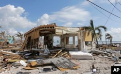 FILE - Debris surrounds a destroyed structure in the aftermath of Hurricane Irma in Big Pine Key, Fla. Rising sea levels and fierce storms have failed to stop relentless population growth along U.S. coasts in recent years, a new Associated Press analysis finds.