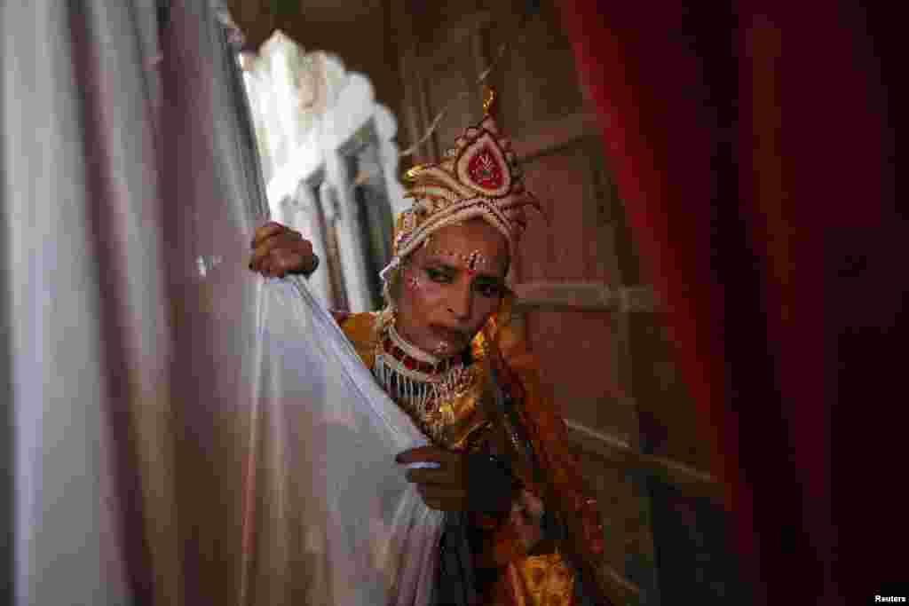 Một bà góa trong trang phục Nữ thần Radha của đạo Hindu hé màn nhìn xuống khán giả trong lễ hội Holi ở bang Uttar Pradesh miền bắc.