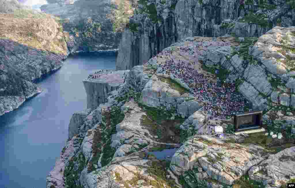 "People gather in the mountains near Preikestolen (The Pullpit Rock) in Forsand near Stavanger, Norway, to see the movie ""Mission: Impossible — Fallout,"" Aug. 1, 2018."