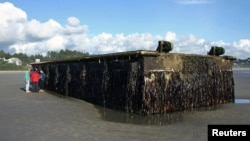 Oregon Parks and Recreation Department photograph shows a very large and heavy dock that washed ashore on Agate Beach, north of Newport, Oregon on June 6, 2012.