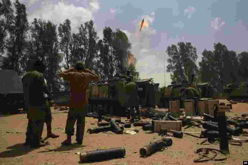 Israeli soldiers fire a mortar shell towards the Gaza Strip, near the Israel - Gaza border, Aug. 4, 2014.