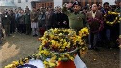یک پلیس هندی به تابوت پلیس کشته شده در حادثه سو قصد به رهبر حزب حاکم منطقه کشمیر زیر کنترل هند، ادای احترام می کند. ۱۲ دسامبر ۲۰۱۱