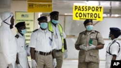 Nigeria health officials wait to screen passengers at the arrival hall of Murtala Muhammed International Airport in Lagos, Nigeria, Monday, Aug. 4, 2014. Nigerian authorities on Monday confirmed a second case of Ebola in Africa's most populous country, an