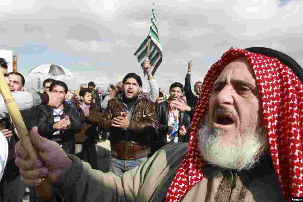 Syrian protesters living in Jordan hold Syrian opposition flags as they shout slogans against Syria's President Bashar al-Assad during a protest outside the Syrian embassy in Amman December 14, 2012. REUTERS/Muhammad Hamed (JORDAN - Tags: POLITICS CIVIL U