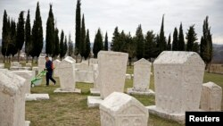 A worker cuts grass at Radimlja necropolis near Stolac, March 10, 2015. The tombstones date to the 12th century and are revered in the Balkans for their unique decorative symbols and carvings, often linked to the medieval Kingdom of Bosnia.