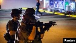 Cảnh sát bảo vệ an ninh để nhân viên cứu hỏa làm việc sau khi cửa hàng Dellwood Market bị cướp phá, trong cuộc biểu tình bạo động gần thị trấn Ferguson, tiểu bang Missouri 17/8/14