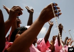 FILE - Women from a Catholic society wave rosary beads as they watch the convoy of Pope Benedict XVI pass on the way to a meeting between the pope and Cameroonian bishops, in Yaounde, March 18, 2009.