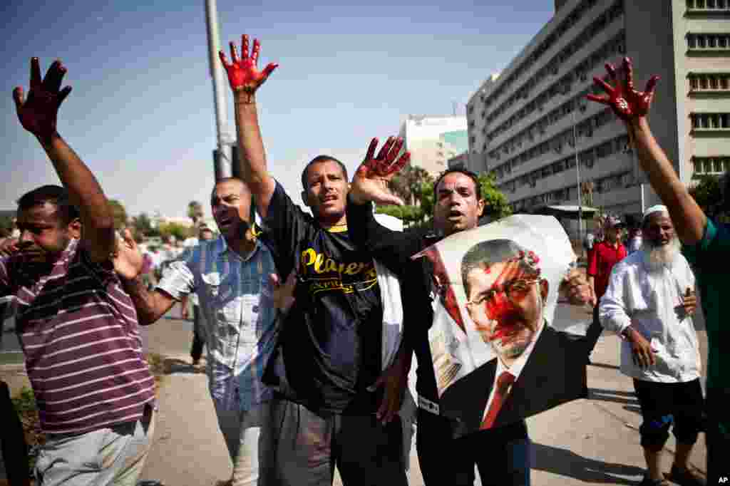 Islamist protesters, one holding a picture of ousted president Mohamed Morsi, hold up blood-stained hands after troops opened fire on a protest in front of the Republican Guard headquarters in Nasr City, Cairo, July 5, 2013