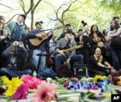People sing John Lennon and Beatles songs as they gather around the Imagine mosaic in Strawberry Fields in New York's Central Park to celebrate the birthday of John Lennon in New York, October 9, 2010.