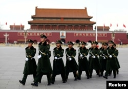 FILE - Paramilitary police walk in formation across Tiananmen Square as the sessions of the National People's Congress are taking place in the nearby Great Hall of the People in Beijing, China, March 6, 2017.