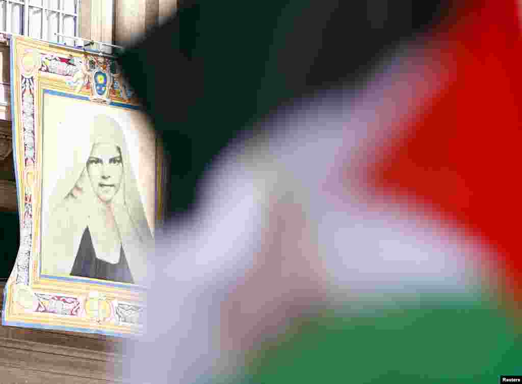 A Palestinian flag waves in front of a tapestry of Mariam Baouardy Haddad before Pope Francis leads a ceremony for the canonization of four nuns at Saint Peter's square in the Vatican City, May 17, 2015.