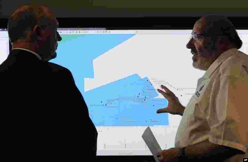 Mike Barton, rescue coordination chief, right, shows Australia's Deputy Prime Minister, Warren Truss, the map of the Indian Ocean search areas during a tour of the Australian Maritime Safety Authority's rescue coordination center in Canberra, March 23, 2014.