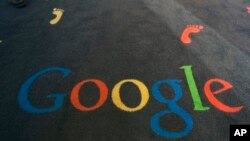 FILE - The Google logo is printed on the carpet during the inauguration of the new Google cultural institute in Paris, Dec. 10, 2013.