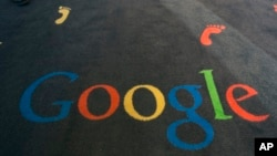 FILE - The Google logo is printed on the carpet during the inauguration of the Google cultural institute in Paris, Dec. 10, 2013.