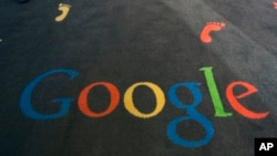 FILE - The Google logo is printed on the carpet of the Google cultural institute in Paris, Dec. 10, 2013.