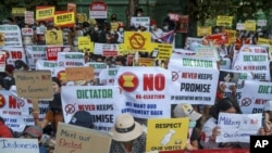Anti-coup protesters display signs near the Indonesian Embassy in Yangon, Myanmar, Wednesday, Feb. 24, 2021. (AP Photo)